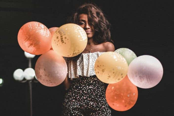 a woman holding varying colors of balloons