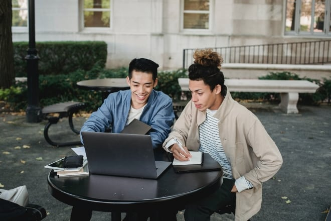 two people sitting in an outdoor table looking at laptop