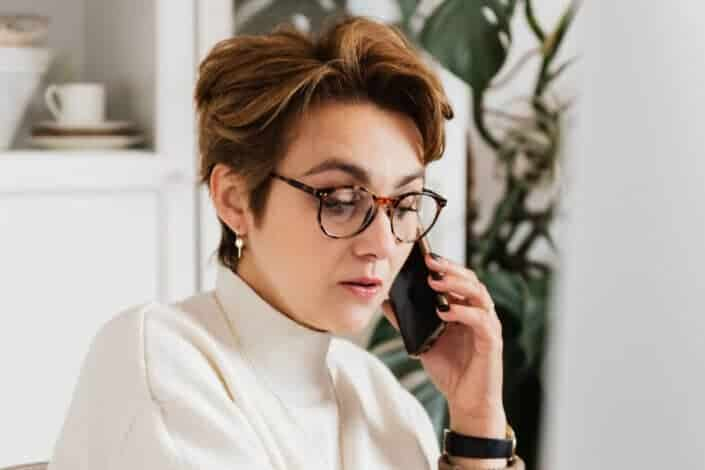a woman with glasses answering her phone