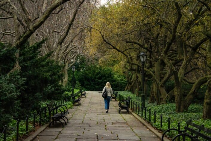 a woman walking alone in the middle of a park