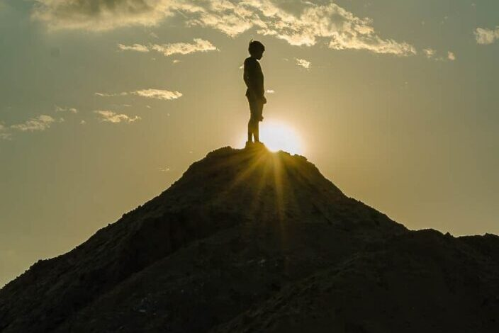 man on top a hill with sunset rays passing through him