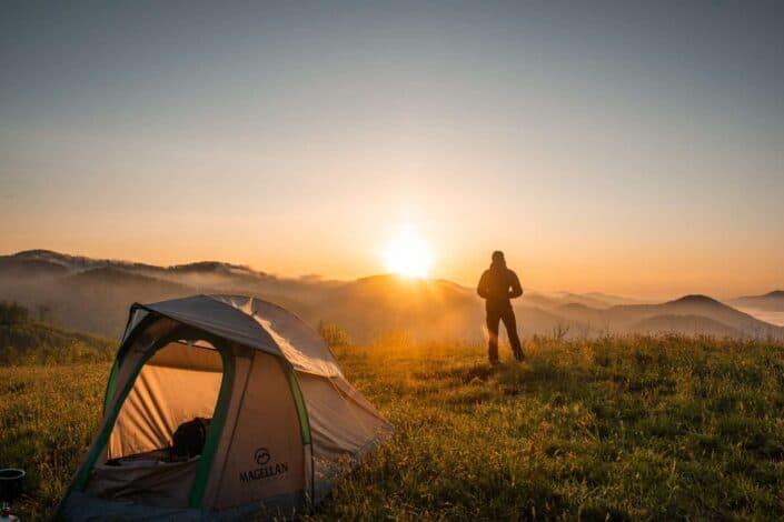 silhouette of man watching sunset near tent