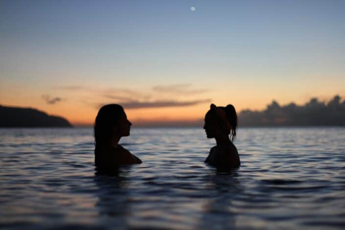 silhouette of two women in the middle of the ocean