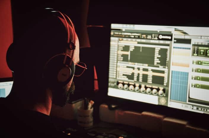 Male dj in headset working on desktop computer
