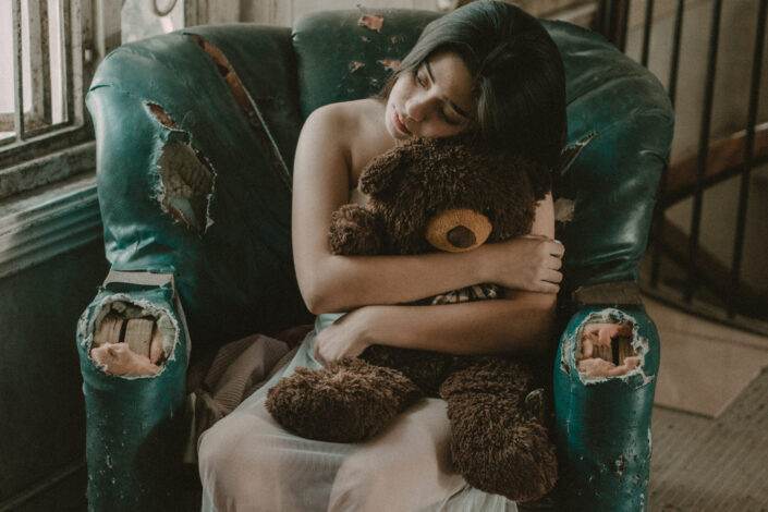 Woman hugging brown bear plush toy while sitting in a worn out green couch