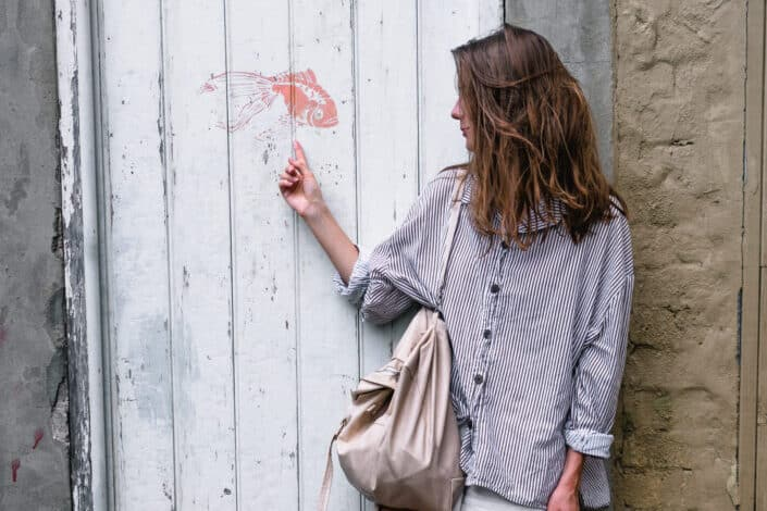 Woman wearing gray long sleeved shirt pointing at a fish painted on a white wall