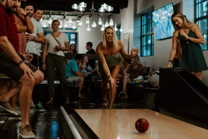 group of people watching woman playing bowling