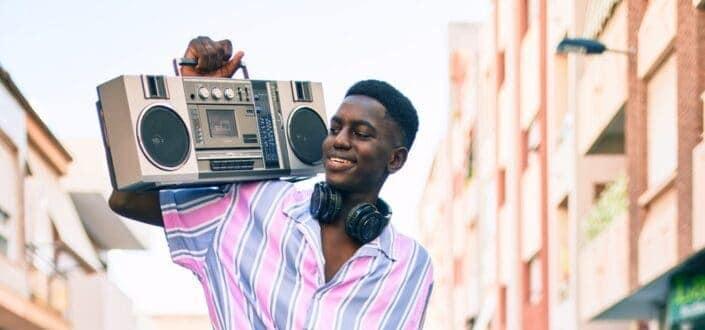 Man listening to music using boom box and headphones
