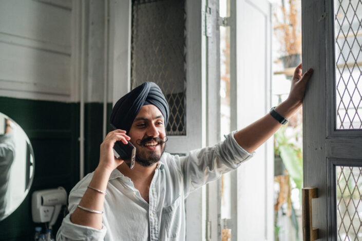 smiling man speaking on smartphone while holding on to a door