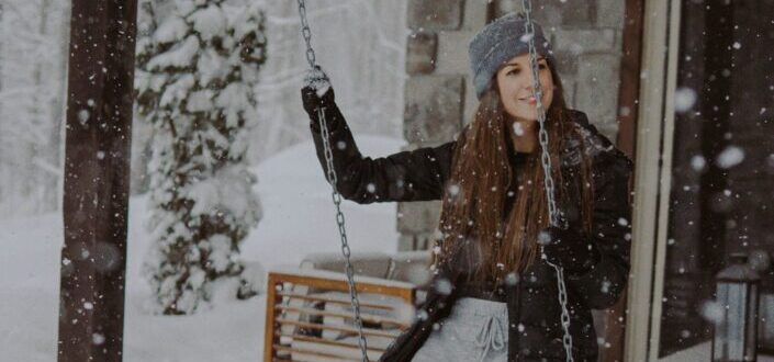 A woman in winter clothes on a swing during winter