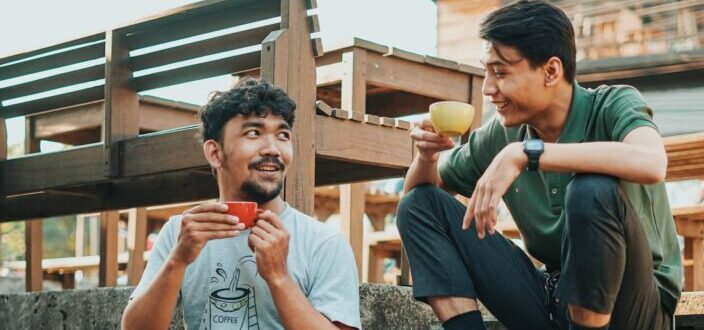 Two guys sipping coffee while sitting on wooden steps outdoors
