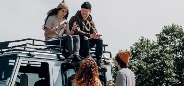 Two people sitting on roof of Jeep with two other people looking at them