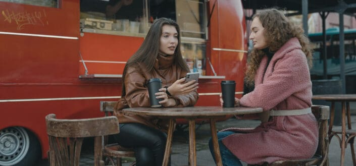 Two friends in deep conversation in front of a food truck
