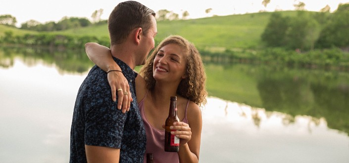 A couple drinking beer by a river