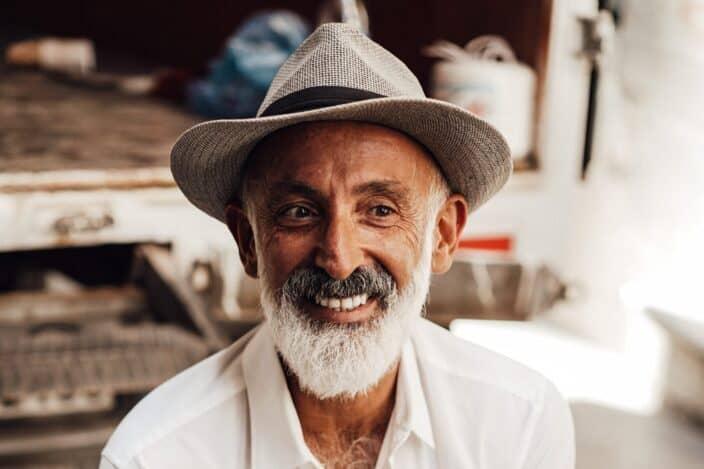Smiling senior man sitting on the street