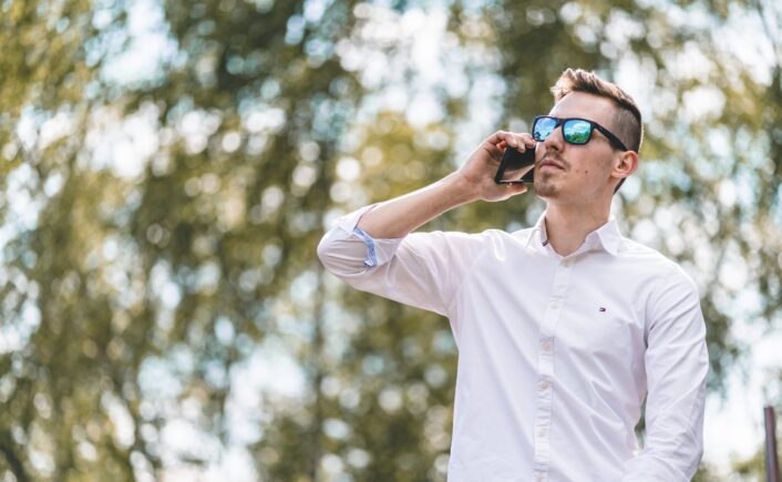 man looking upwards while on the phone
