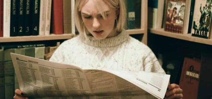 Girl reading a newspaper with a shocked face
