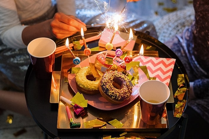 Donuts with candles and party sparkles.