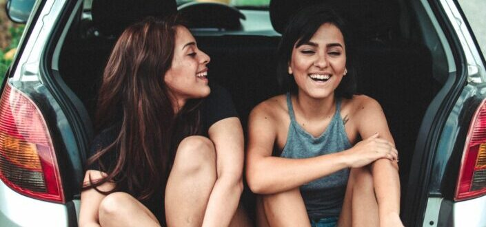 Two girls sitting on trunk