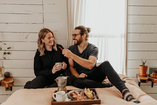 Young couple being playful while having breakfast in bed - Food pick up lines
