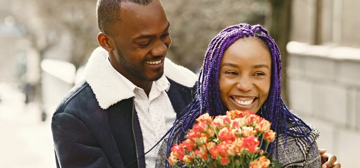 A couple smiling while the woman holds flowers