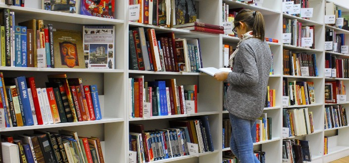 Girl reading a book in front of a bookshelf
