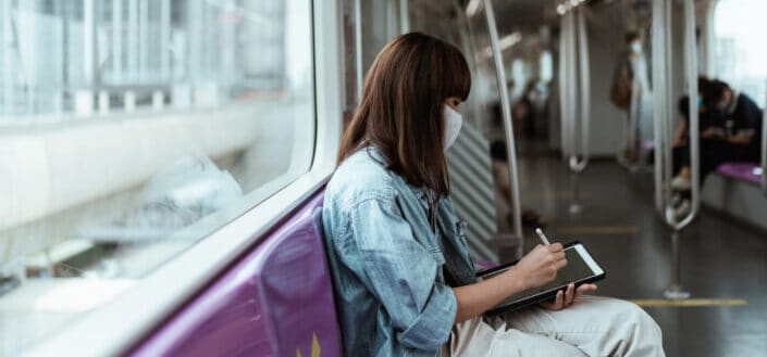 Girl sitting on train writing on her tablet