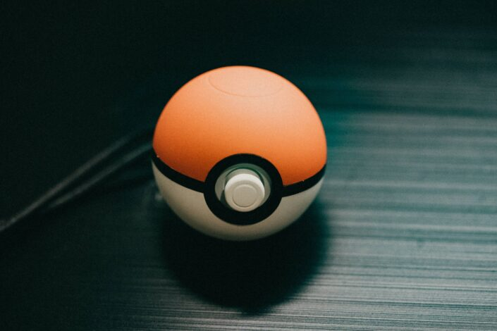 a pokeball laying on a black surface