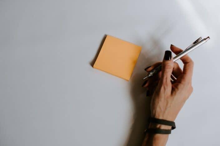 A hand holding a pen near a sticky note.