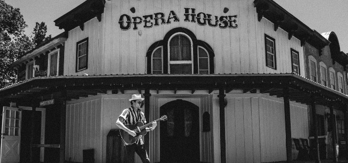 Man playing a guitar in front of an Opera House
