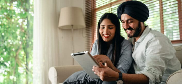 Couple smiling at a tablet