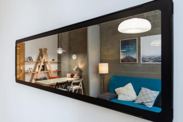 Long mirror reflecting a small condo unit