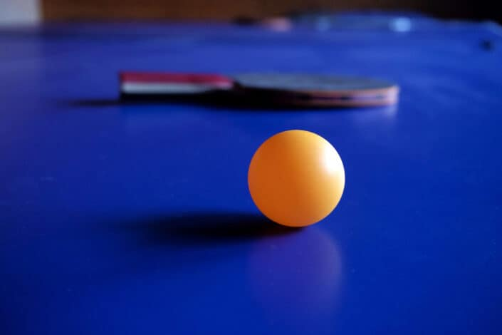 Yellow ping pong ball and paddle on a blue table