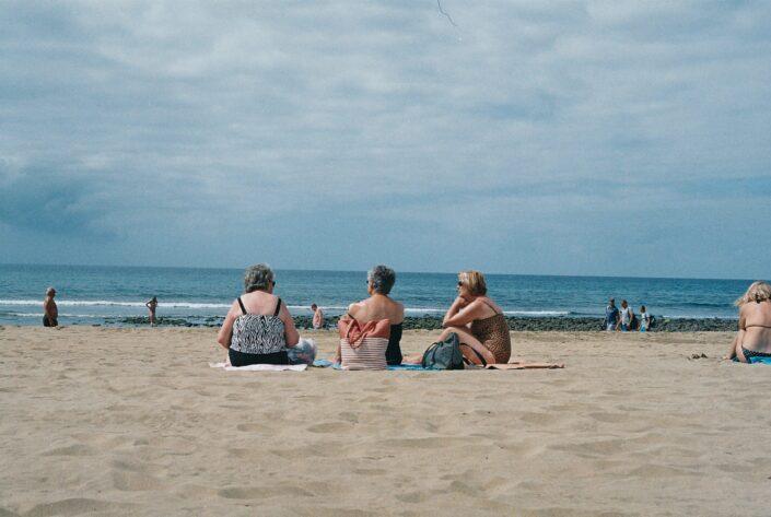 Three senior ladies sitting on a beach