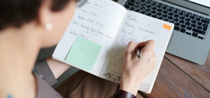 Woman scribbling notes on an open notebook