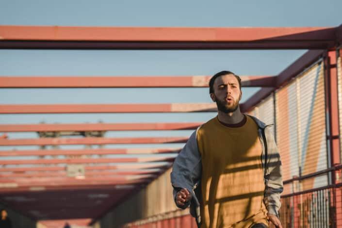 Guy jogging on a bridge
