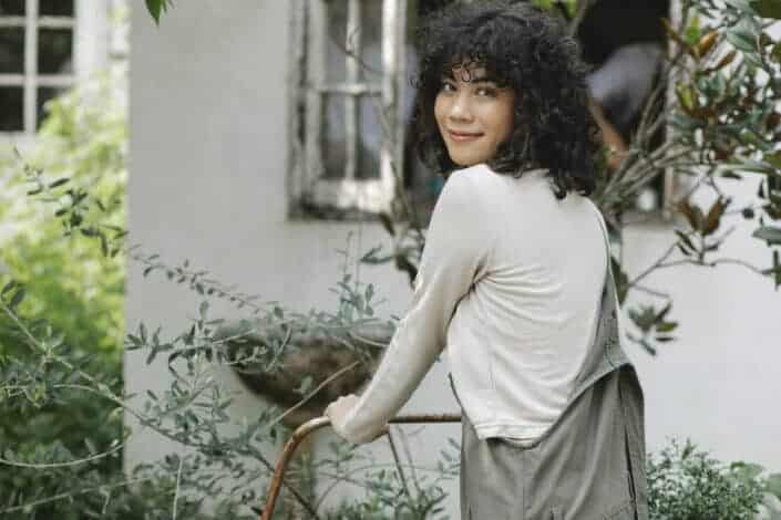 Curly haired woman rolling a garden cart