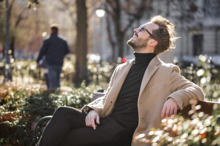 Happy man sitting on a bench