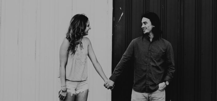 couple holding hands in contrasting background