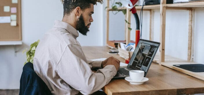 A man scrolling on his laptop