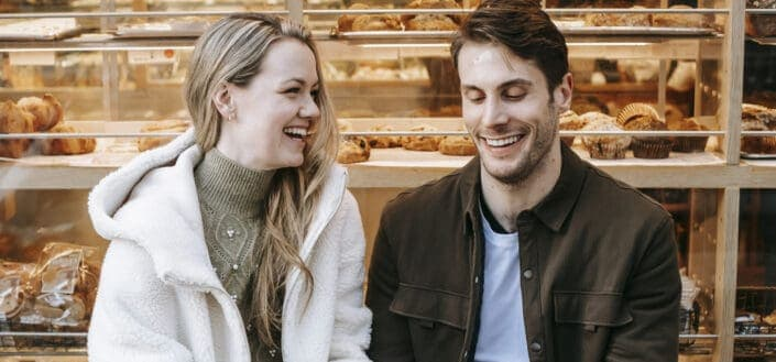 Cheerful young couple holding hands during date in bakery
