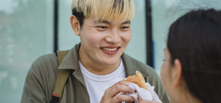 Cheerful asian guy grinning at girl while eating