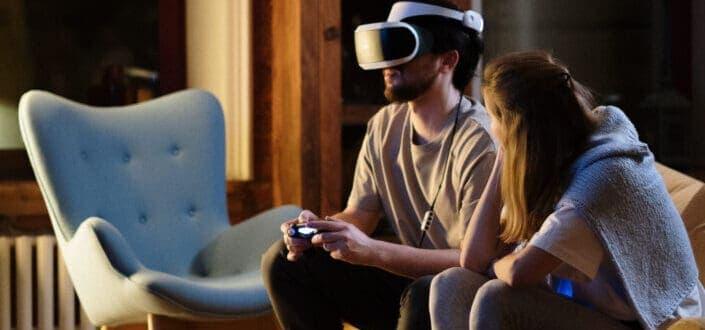 Woman looking at man playing VR