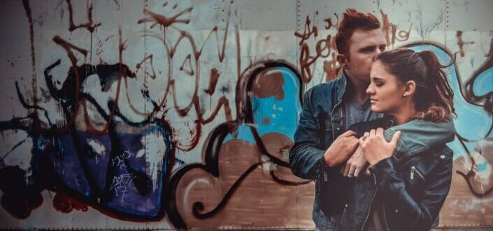 A couple in leather jackets by a wall graffiti