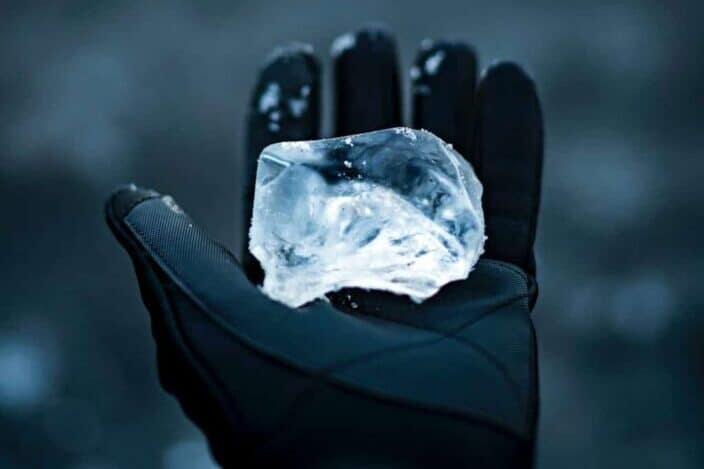 Hand wearing gloves holding an ice