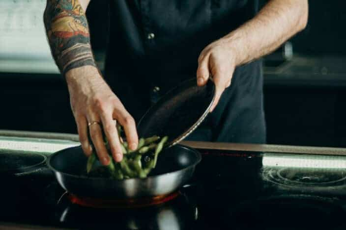 Tattooed guy cooking beans