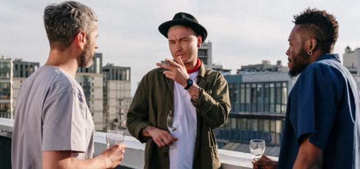 Three male friends talking on a rooftop