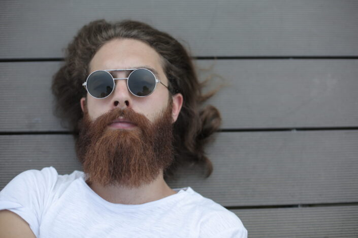 man with shades lying at the ground