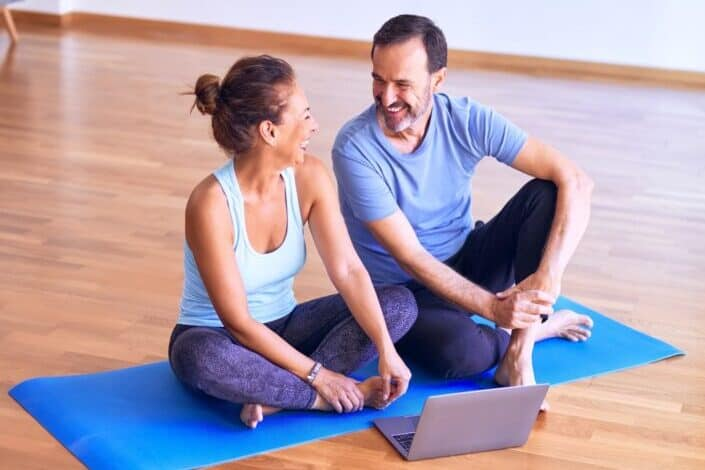 a couple laughing while sitting on yoga mat