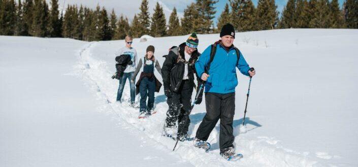 friends trekking through the mountains during snow